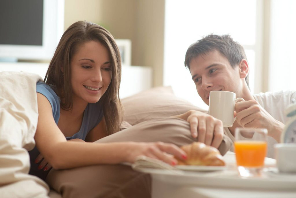 couple enjoying breakfast in bed at Clayton Hotel Manchester Airport