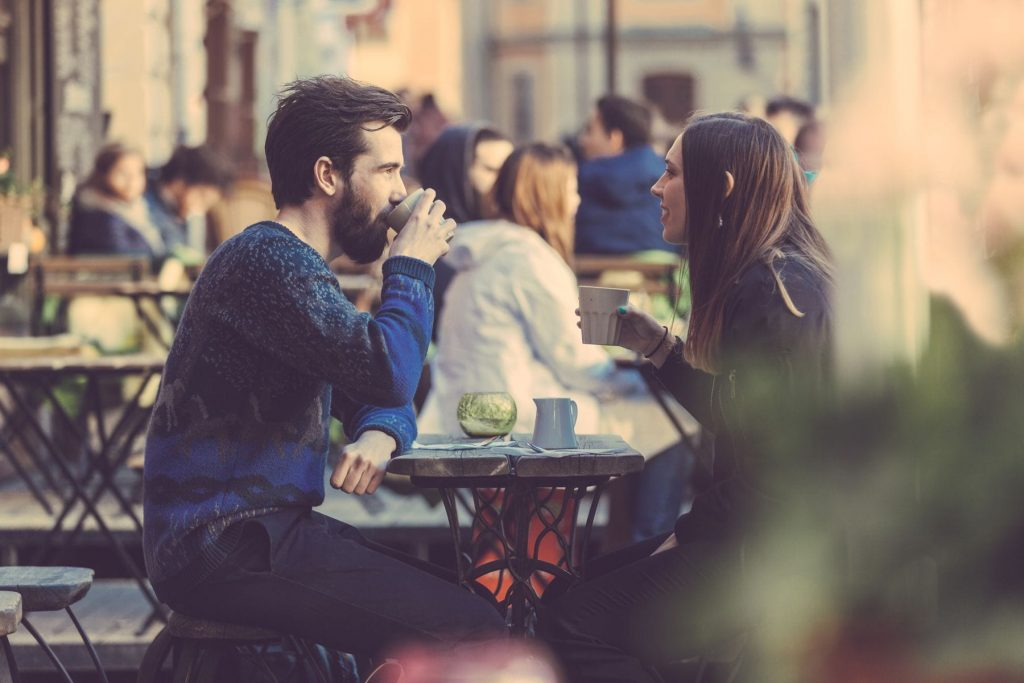 couple having coffee outside busy cafe