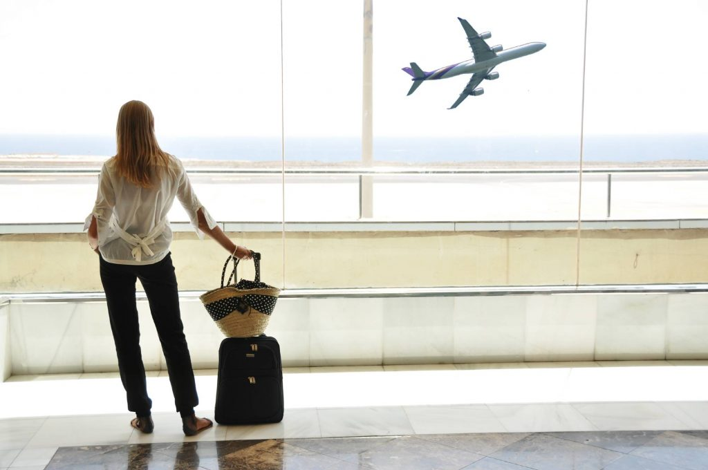 woman with suitcase watching an airplane takeoff